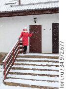 Estate agent showing inviting to enter a house for visit, winter season. Стоковое фото, фотограф Кекяляйнен Андрей / Фотобанк Лори