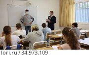 Portrait of diligent teenager schoolboy wearing protective face mask answering at board to teachers question in front of group of students in classroom, new normal education during pandemic. Стоковое видео, видеограф Яков Филимонов / Фотобанк Лори