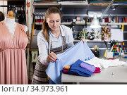 Female seamstress is looking on textile for create new dress. Стоковое фото, фотограф Яков Филимонов / Фотобанк Лори