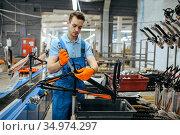 Bicycle factory, worker holds teen bike frame. Стоковое фото, фотограф Tryapitsyn Sergiy / Фотобанк Лори