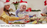 Caucasian senior woman in santa hat pouring drink in glass of woman while sitting on dining table an. Стоковое видео, агентство Wavebreak Media / Фотобанк Лори