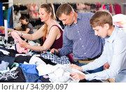 Mother,father and son choosing wear at the clearance sale shop. Стоковое фото, фотограф Яков Филимонов / Фотобанк Лори