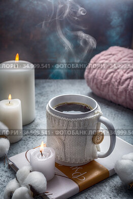 Cup of hot drink in white knitted cover placed on the book candles and cotton around hugge style