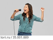 happy asian woman with microphone singing. Стоковое фото, фотограф Syda Productions / Фотобанк Лори