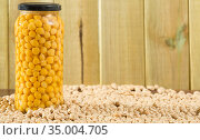 Glass jar with boiled chickpeas and bowl of raw chickpea grains on wooden surface. Стоковое фото, фотограф Яков Филимонов / Фотобанк Лори
