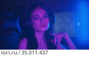 Young attractive woman with light makeup sitting in neon gaming club - smiling and looking in the camera. Стоковое видео, видеограф Константин Шишкин / Фотобанк Лори