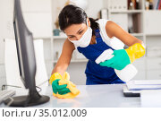 Kazhahstani woman wearing uniform ana mask cleaning at office. Стоковое фото, фотограф Яков Филимонов / Фотобанк Лори