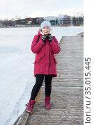 Full length portrait of an adult woman wearing warm coat with hood on head and knit mittens standing on quay of frozen lake. Стоковое фото, фотограф Кекяляйнен Андрей / Фотобанк Лори