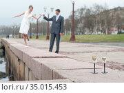 Newlywed couple walking on embarkment, two stem glasses with champagne standing on granite. Стоковое фото, фотограф Кекяляйнен Андрей / Фотобанк Лори