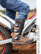 Close up view of motocross boot standing on peg of trial motorcycle. Safety footwear and apparel for riding. Стоковое фото, фотограф Кекяляйнен Андрей / Фотобанк Лори
