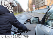 Motorcyclist stands by side with a car on the road, lateral rear mirrors are close to each other, touching during movement. Стоковое фото, фотограф Кекяляйнен Андрей / Фотобанк Лори