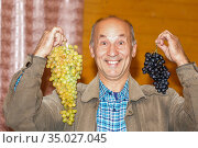 Mature emotional man holds two clusters of ripe grapes in his hands. Стоковое фото, фотограф Акиньшин Владимир / Фотобанк Лори