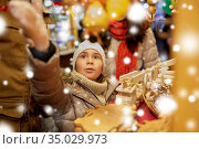 happy family buying souvenirs at christmas market. Стоковое фото, фотограф Syda Productions / Фотобанк Лори