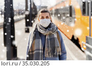 woman in protective face mask at railway station. Стоковое фото, фотограф Syda Productions / Фотобанк Лори