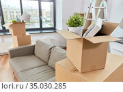 sofa and corrugated boxes with stuff at new home. Стоковое фото, фотограф Syda Productions / Фотобанк Лори