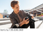 young man with camera photographing in city. Стоковое фото, фотограф Syda Productions / Фотобанк Лори