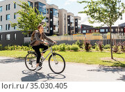 young man riding bicycle on city street. Стоковое фото, фотограф Syda Productions / Фотобанк Лори