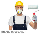 worker or builder in respirator with paint roller. Стоковое фото, фотограф Syda Productions / Фотобанк Лори