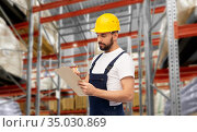 male loader or worker with clipboard at warehouse. Стоковое фото, фотограф Syda Productions / Фотобанк Лори