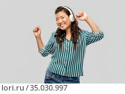asian woman in headphones listening to music. Стоковое фото, фотограф Syda Productions / Фотобанк Лори