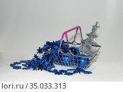 Синие, яркие, блестящие бубенцы и бусы, серебряная елка-подвеска для украшения елки в маленькой декоративной интерьерной корзинке на светлом фоне. Редакционное фото, фотограф Меркулова Наталья Геннадьевна / Фотобанк Лори