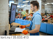 Bicycle factory, worker manages bike assembly line. Стоковое фото, фотограф Tryapitsyn Sergiy / Фотобанк Лори