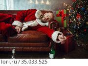 Bad drunk Santa claus sleeps on sofa after party. Стоковое фото, фотограф Tryapitsyn Sergiy / Фотобанк Лори