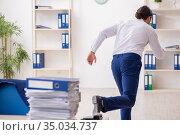 Young businessman unhappy with excessive work in the office. Стоковое фото, фотограф Elnur / Фотобанк Лори