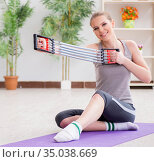 Young woman exercising with resistance band in gym. Стоковое фото, фотограф Elnur / Фотобанк Лори