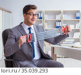 Young businessman exercising with elastic expander in office. Стоковое фото, фотограф Elnur / Фотобанк Лори