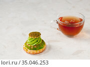 Shu cake with pistachio cream and tea on the table, space for text. Стоковое фото, фотограф Катерина Белякина / Фотобанк Лори