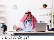 Old male arab doctor cardiologist working in the clinic. Стоковое фото, фотограф Elnur / Фотобанк Лори