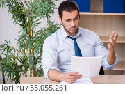 Young male bookkeeper working in the office. Стоковое фото, фотограф Elnur / Фотобанк Лори