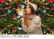 woman in knitted hat sending christmas magic. Стоковое фото, фотограф Syda Productions / Фотобанк Лори