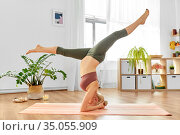 pregnant woman doing yoga headstand split at home. Стоковое фото, фотограф Syda Productions / Фотобанк Лори