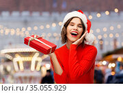 happy young woman in santa hat with red gift box. Стоковое фото, фотограф Syda Productions / Фотобанк Лори