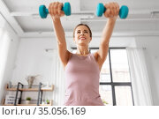smiling young with dumbbells exercising at home. Стоковое фото, фотограф Syda Productions / Фотобанк Лори