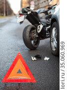 Emergency road triangle sign is on asphalt, road accident with car and motorcycle. Стоковое фото, фотограф Кекяляйнен Андрей / Фотобанк Лори