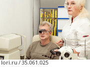 Doctor ophthalmologist checks the vision of patient. Стоковое фото, фотограф Юлия Бабкина / Фотобанк Лори