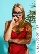 Sportive woman in red swimsuit poses on cyan. Стоковое фото, фотограф Tryapitsyn Sergiy / Фотобанк Лори