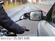 Motorcycle rider touching side mirror of a car when riding nearby on a road, close up view. Стоковое фото, фотограф Кекяляйнен Андрей / Фотобанк Лори