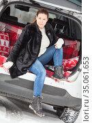 Portrait of young woman dressing black fur coat sitting in car in the trunk, winter season. Стоковое фото, фотограф Кекяляйнен Андрей / Фотобанк Лори