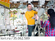 Man and girl are choosing stylish round matt glass ceiling lamp. Стоковое фото, фотограф Яков Филимонов / Фотобанк Лори