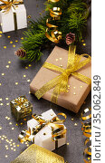 Christmas concept. Bright gift wrap with gold ribbon, christmas branches and confetti stars on dark background. Стоковое фото, фотограф Сергей Молодиков / Фотобанк Лори