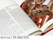 Раскрытая книга в твёрдом переплёте на белом фоне. Редакционное фото, фотограф Игорь Низов / Фотобанк Лори