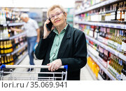 older woman with glasses talking on the phone in the supermarket. Стоковое фото, фотограф Татьяна Яцевич / Фотобанк Лори