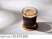 glass of coffee on cork drink coaster. Стоковое фото, фотограф Syda Productions / Фотобанк Лори
