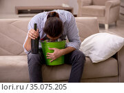 Young drunk man suffering at home. Стоковое фото, фотограф Elnur / Фотобанк Лори