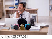 Young male employee afraid of missing deadline at workplace. Стоковое фото, фотограф Elnur / Фотобанк Лори