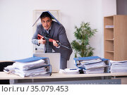 Young employee angry with excessive work holding firearm weapon. Стоковое фото, фотограф Elnur / Фотобанк Лори